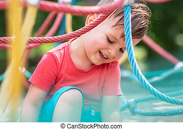 little boy playing in the rope net on the playground
