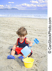 Little boy playing in the sand at the beach