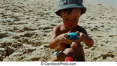 Little boy playing in the sand on tropical beach