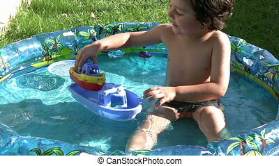 Little boy playing in wading pool