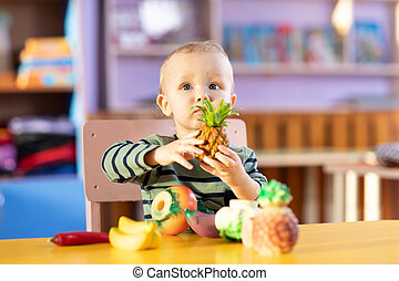 Little boy playing indoors at home or kindergarten. Adorable child with plastic vegetables and fruits.