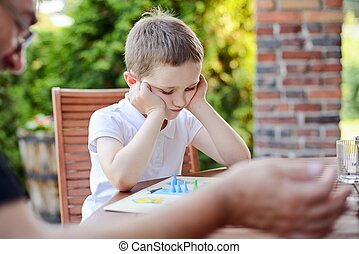 Little boy playing ludo board game on the terrace