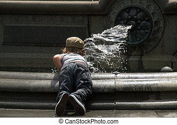 Little boy playing on a fountain