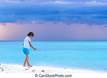 Little boy playing on a tropical beach at sunset