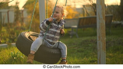 Little boy playing on swing in backyard at coutryside. Happy Boy on Swing.