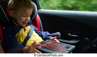 Little boy playing on tablet computer in the car