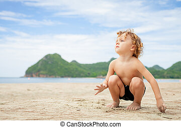 Little boy playing on the beach.