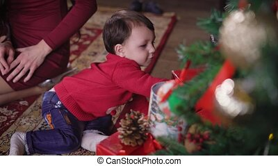 Little boy playing on the rug and trying to get a box with a gift that lies under the Christmas tree. The child very carefully looking at the camera.