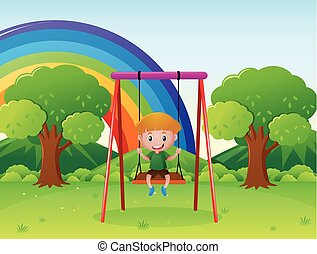 Little boy playing on the swing in the park