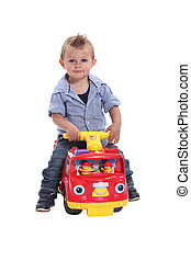 Little boy playing on toy car