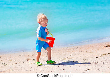 Little boy playing on tropical beach