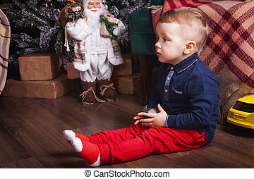 little boy playing toy car near christmas decorum