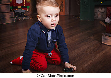 little boy playing toy car sitting on the floor