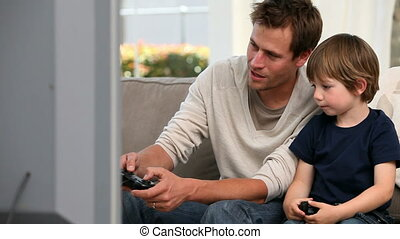 Little boy playing videogames with his father