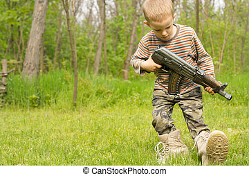 Little boy playing with a gun in the countryside