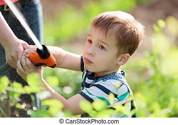 Little boy playing with a jet of water in a garden