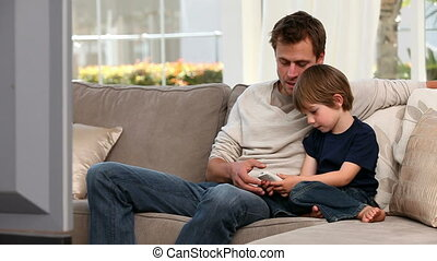 Little boy playing with a remote control near his father in...