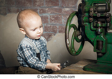 little boy playing with a spanner