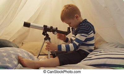Little boy playing with a telescope in children's tent at ...