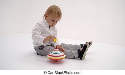 Little boy playing with a whirligig. on white background.