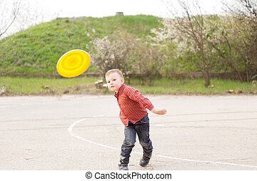 Little boy playing with a yellow frisbee