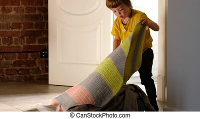 Crop little boy covering heap of clothes with knitted blanket in cozy room at home