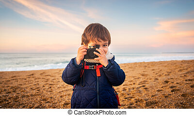 Little boy playing with camera on beach at sunset