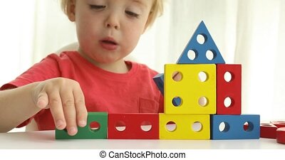Little boy playing with colorful block building a house