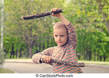 Little boy playing with fighting sticks
