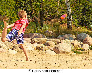 Little boy playing with frisbee disc.