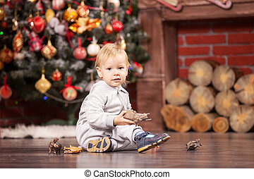 Little boy playing with his toy by Christmas tree