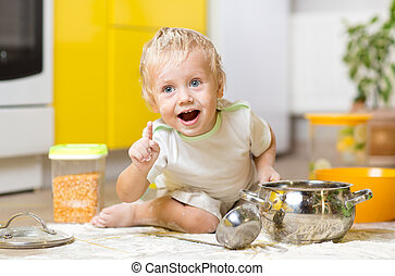 Playful child boy with kitchenware and foodstuffs on floor in kitchen