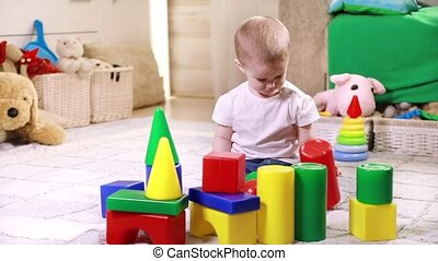 Little boy playing with plastic blocks