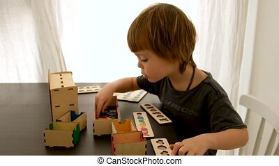 Adorable little boy in t shirt sitting at table and playing with puzzle and wooden boxes on weekend day at home