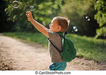 Little boy playing with soap bubbles in summer park on sunny day