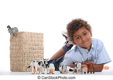 Little boy playing with toy animals