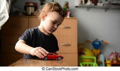 little boy playing with toy car in the children's room
