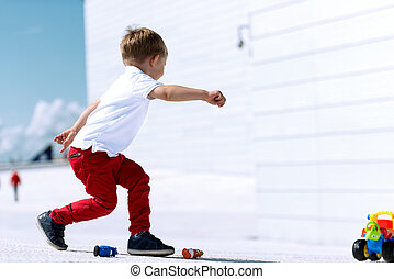 Little boy playing with toy car running