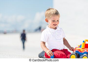 Little boy playing with toy car with copy space