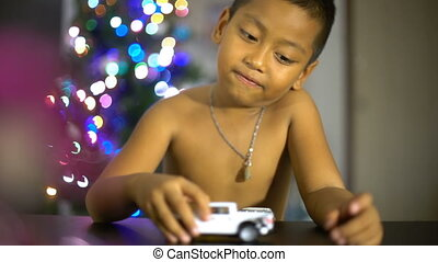 Little boy playing with toy cars in living room