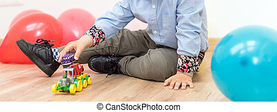 Little boy playing with toy cars on the floor indoors.