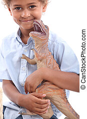 Little boy playing with toy dinosaur