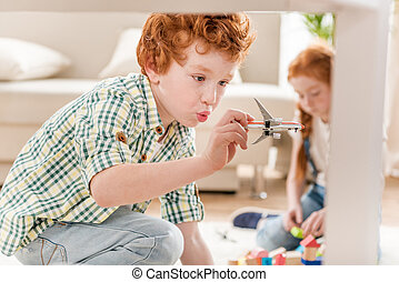 little boy playing with toy plane while sister playing with cubes