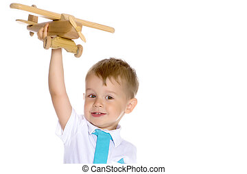 Little boy playing with wooden plane