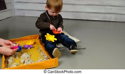 Little boy playing with wooden railway
