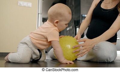 Little boy playing with yellow ball and his mother at home.
