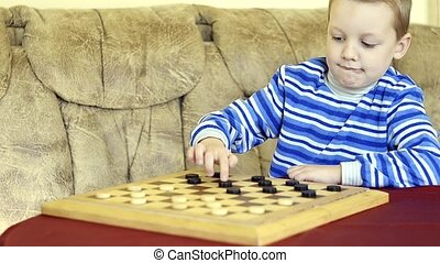 little boy plays checkers with his