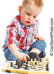 Little boy plays chess.