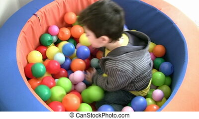 Little boy plays in ball pit