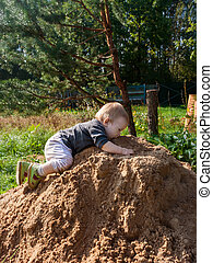 little boy plays in King of the Hill on a pile of orange fresh wet sand. kid tastes sand from the very top of the hill
